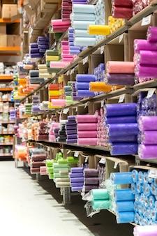 Negozio di tessuti con rotoli di tessuto sugli scaffali assortimento di vestiti colorati in vendita in magazzino
