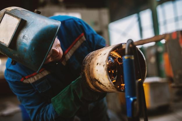Operaio di tessuto in tubo di metallo di taglio uniforme protettiva sul tavolo di lavoro con una smerigliatrice elettrica nell'officina industriale.