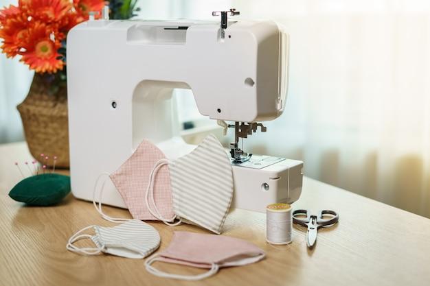 Tessuti, accessori per cucire e macchina da cucire per cucire una maschera anti-virus durante la pandemia di coronavirus.