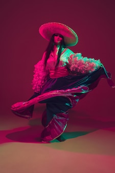 Favolosa ballerina di cinco de mayo sulla parete viola dello studio alla luce al neon