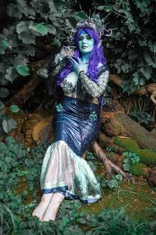 Favolosa sirena scura con la pelle blu nel primo piano della foresta