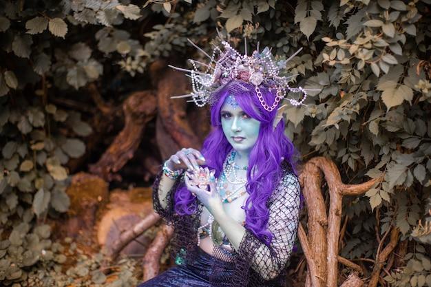 Sirena favolosa con pelle blu in primo piano del fogliame