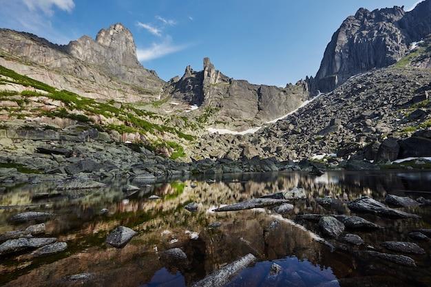Favolose montagne e laghi, viaggi ed escursioni, vegetazione lussureggiante e fiori intorno. acqua di sorgente scongelata dalle montagne. viste magiche di alte montagne, prati alpini