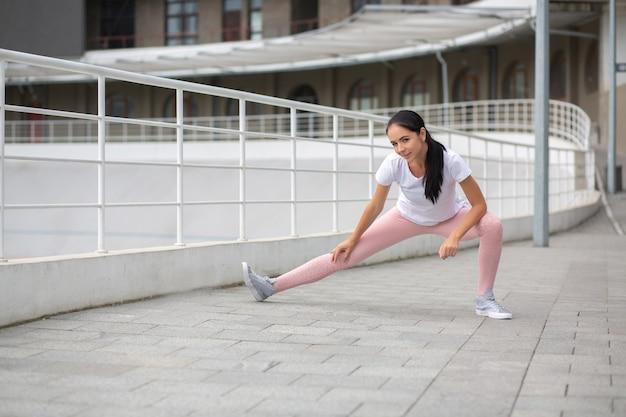 Favolosa ragazza abbronzata che indossa abiti sportivi facendo stretching allo stadio. spazio per il testo