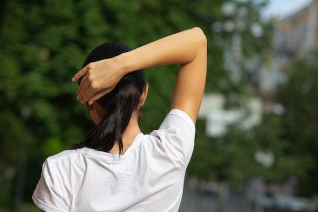 Favolosa ragazza sportiva abbronzata che fa allenamento di stretching al parco. spazio per il testo