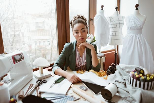 Favoloso giovane sarto in studio di design giovane donna vicino alla macchina da cucire