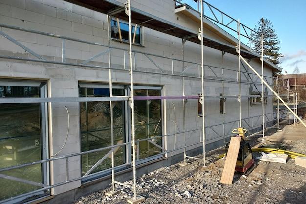 Facciata di un edificio realizzato con blocchi bianchi con grandi finestre in costruzione.
