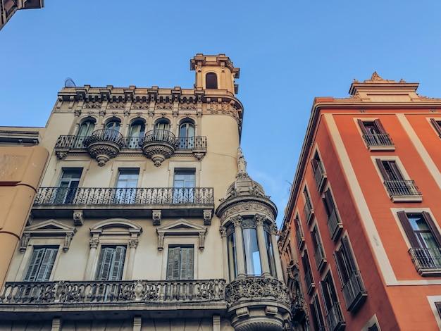 Facciata di edifici nel centro della città spagnola di barcellona. l'edificio è grigio e arancione contro il cielo azzurro.
