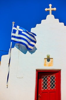 Facciata della chiesa greco-ortodossa con bandiera greca, mykonos, greece