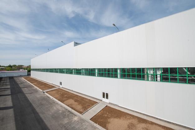 Facciata di un edificio industriale e magazzino in lunghezza con un posto per aiuole e piante