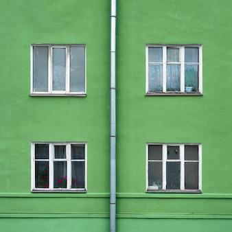 Facciata di vecchio edificio residenziale con finestre e tubo di scarico