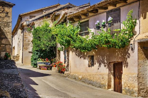 Facciata di vecchia casa in pietra con fiore all'ingresso.