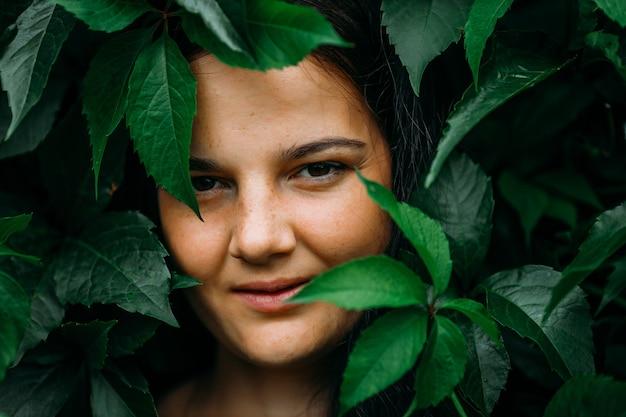 Volto di una giovane e bella donna con le lentiggini ricoperte di foglie. ritratto di modello di bellezza con ciglia naturali o. spa, cura della pelle e benessere. vicino.