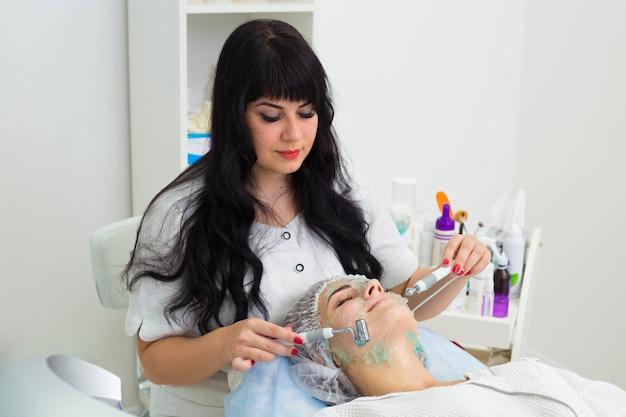 Trattamento di bellezza per il viso. donna che ottiene terapia darsonval facciale utilizzando d'arsonval ad alta frequenza
