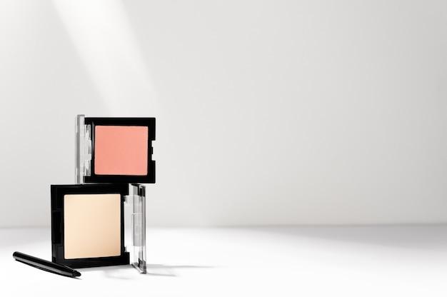 Face beige cipria, blush rosa e pennello professionale maquillage su bianco