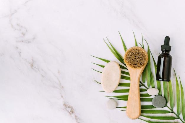 Spazzola per il viso e bottiglia con siero su foglia di palma bellezza e concetto spa flat lay