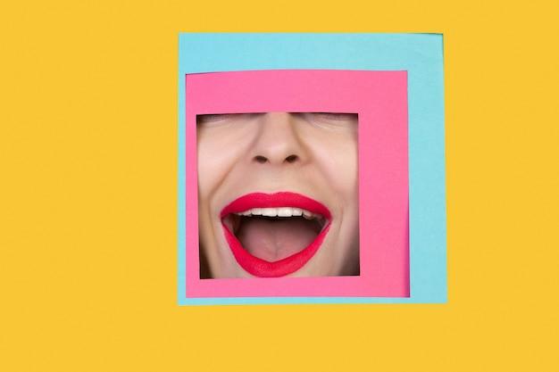 Volto di donna caucasica che sbircia attraverso il quadrato in sfondo giallo