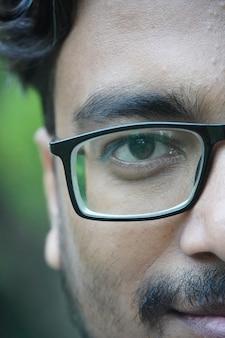 Immagine del primo piano del viso ragazzo adulto nel parco che si diverte e gioca a guardare gli occhiali