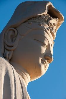 Primo piano del viso della statua di ryozen kannon bodhisattva avalokitesvara, illuminata da una straordinaria luce solare.