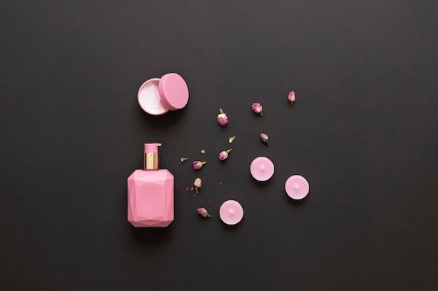 Crema per il viso e lozione per il corpo con estratto di rosa candele profumate rosa e fiori secchi rosa su sfondo nero con posto per il testo