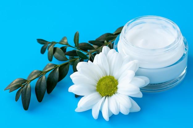 Crema per il viso in una bottiglia di vetro con fiore margherita bianca su sfondo blu. cosmetico naturale a base di erbe, concetto di cura della pelle. fiore di camomilla e ramo verde.