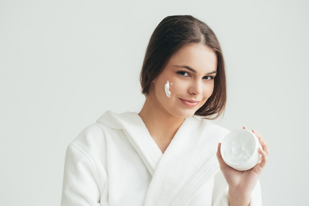 Crema viso donna che applica crean sul ritratto naturale della pelle. colpo dello studio.