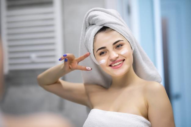 Crema per il viso. giovane bella donna che indossa una camicia bianca che mette la crema per il viso sulla sua bella pelle sana in bagno