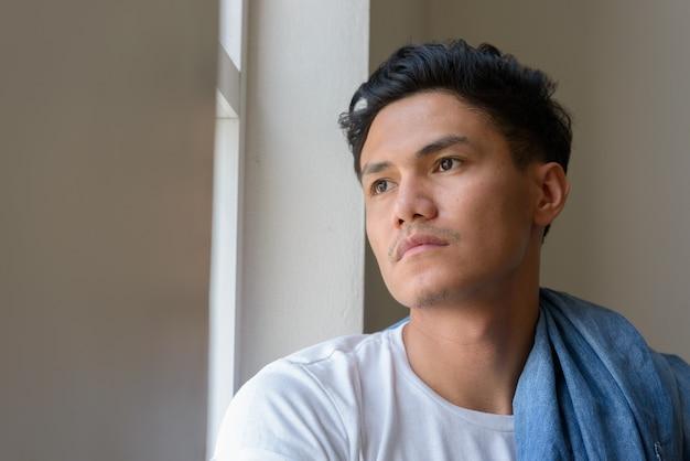 Volto di bell'uomo asiatico guardando fuori dalla finestra al chiuso