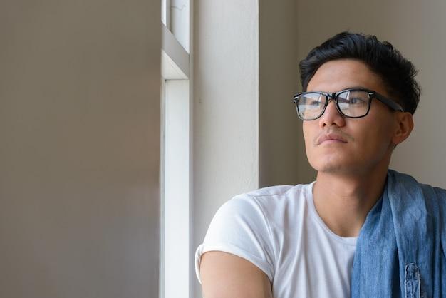 Volto di bell'uomo asiatico con gli occhiali guardando fuori dalla finestra