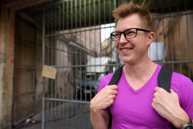 Fronte dell'uomo felice del viaggiatore con zaino e sacco a pelo che esplora intorno alla città di bangkok