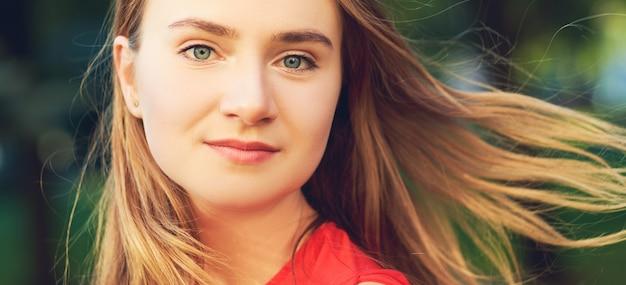 Volto di bella donna felice con capelli volanti in posa per strada in estate in abito rosso.