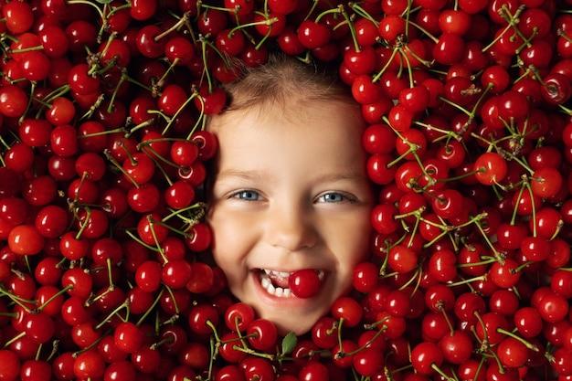 Il volto di un bambino allegro felice circondato da un gran numero di ciliegie rosse mature e succose