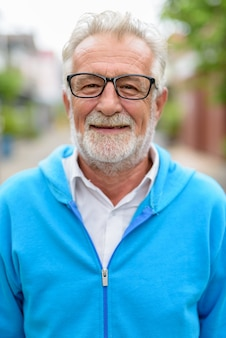 Volto di uomo barbuto senior bello felice sorridente mentre indossa giacca blu e occhiali all'aperto