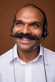 Volto di uomo d'affari indiano felice con i baffi come rappresentante del call center