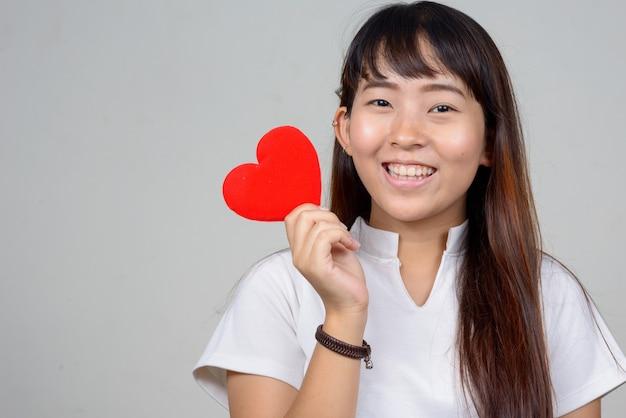 Volto di felice giovane donna asiatica tenendo il cuore pronto per il giorno di san valentino