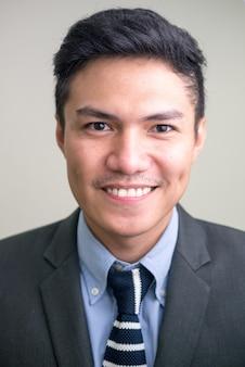 Volto di felice giovane uomo d'affari asiatico bello sorridente