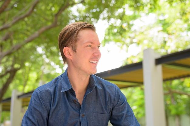 Volto di felice giovane uomo d'affari biondo bello pensando al parco all'aperto