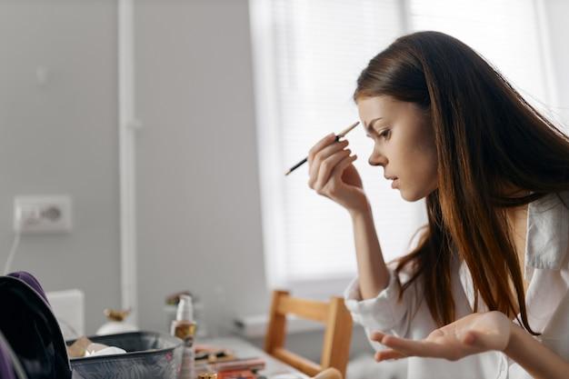Donna di trucco viso con eyeliner al chiuso. foto di alta qualità