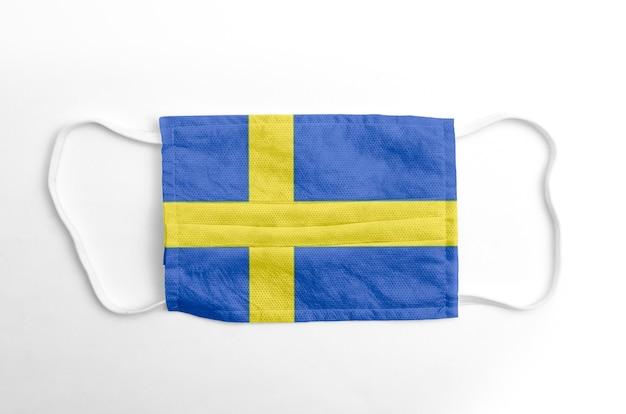 Maschera facciale con bandiera svedese stampata, su fondo bianco.
