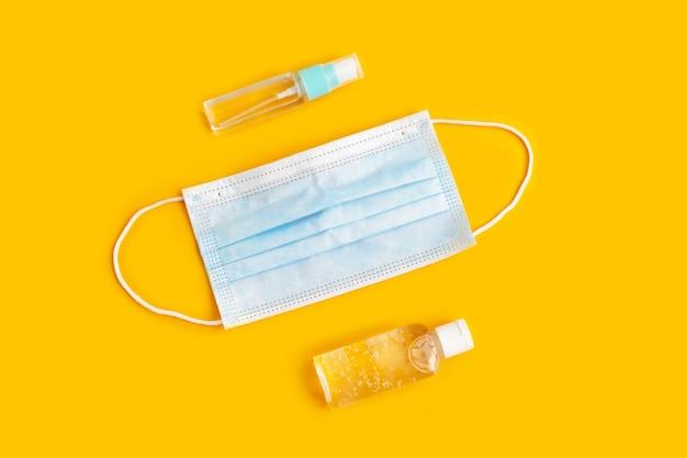 Maschere per il viso e bottiglie di disinfettante per le mani su giallo