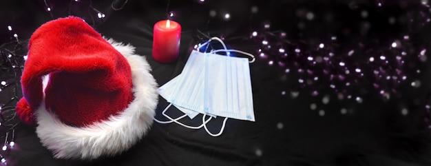 Maschere per il viso indossate accanto a un cappello rosso di babbo natale e una candela sullo sfondo di luci sfocate