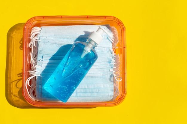 Maschere per il viso con disinfettante gel liquido alcolico sulla superficie gialla