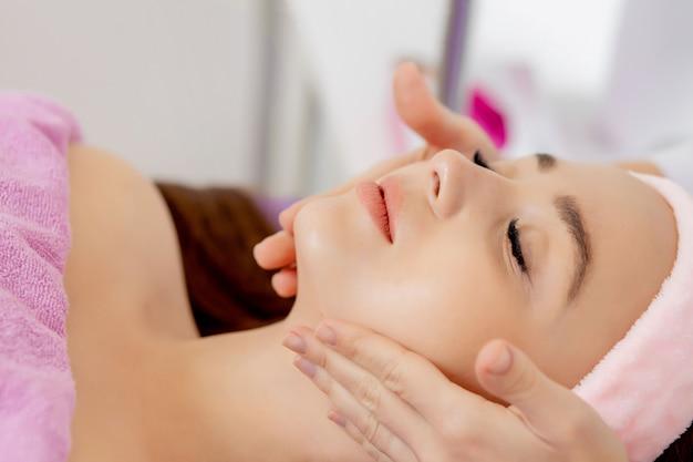 Massaggio viso. primo piano della giovane donna che ottiene trattamento di massaggio della stazione termale al salone della stazione termale di bellezza. cura della pelle e del corpo di spa. trattamento di bellezza del viso. cosmetologia.
