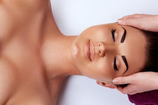 Massaggio al viso. primo piano di giovane donna che ottiene trattamento di massaggio termale al salone della stazione termale di bellezza