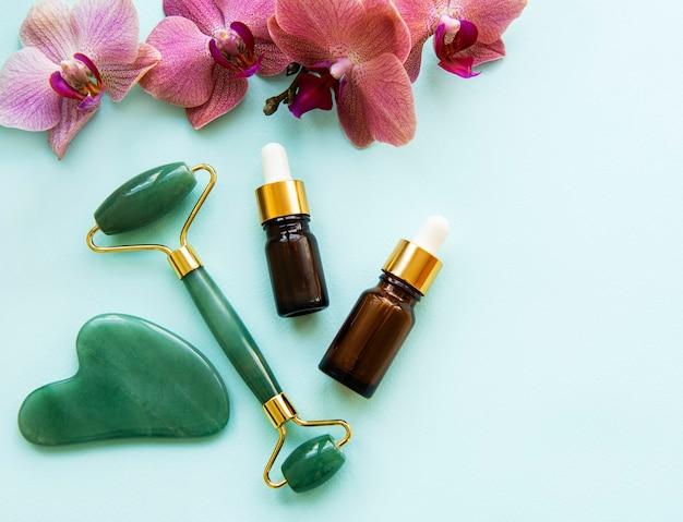 Rullo di giada massaggio viso con prodotto cosmetico sul tavolo verde pastello