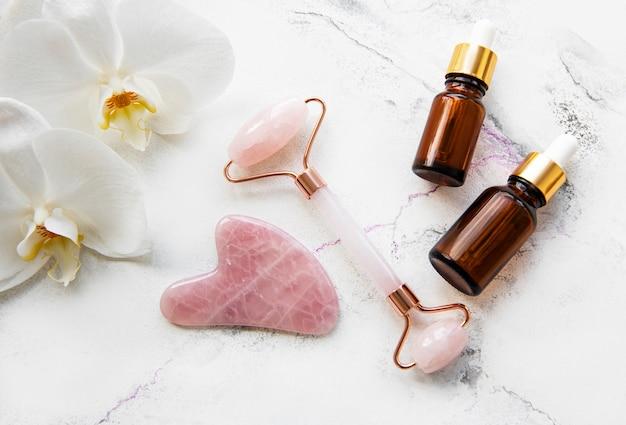 Rullo di giada massaggio viso con prodotto cosmetico sul tavolo di marmo bianco