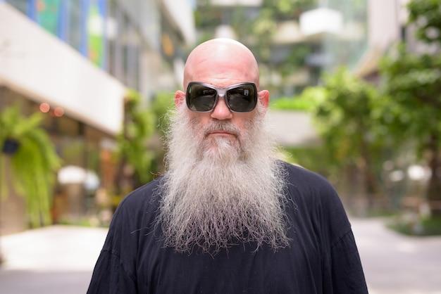 Volto di uomo barbuto calvo bello maturo indossando occhiali da sole con la natura in città