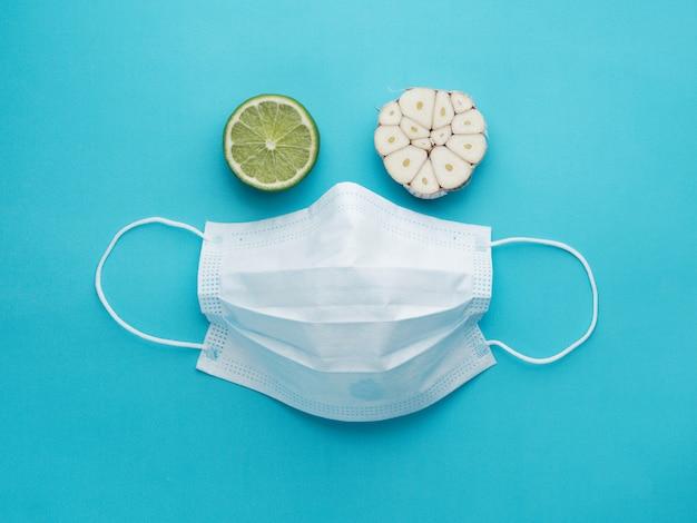 Volto di maschera medica, aglio e limone, sfondo blu. rafforzare il sistema immunitario e proteggere dai virus.