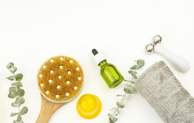 Olio per il viso e rullo per il viso, spazzola per massaggio a secco e un asciugamano di cotone giacciono su un vassoio di legno