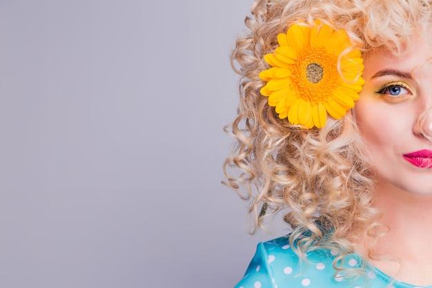 Faccia parte della bella ragazza bionda con voluminosa acconciatura riccia, in una camicetta blu a pois